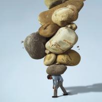 человек под грузом камней